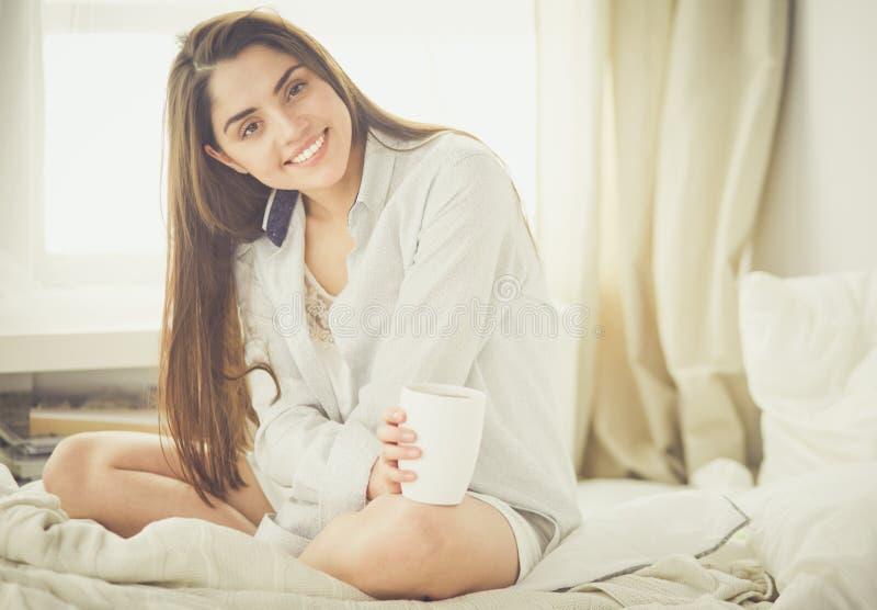 Женщина сидя в кровати читая книгу и имея завтрак стоковое фото rf