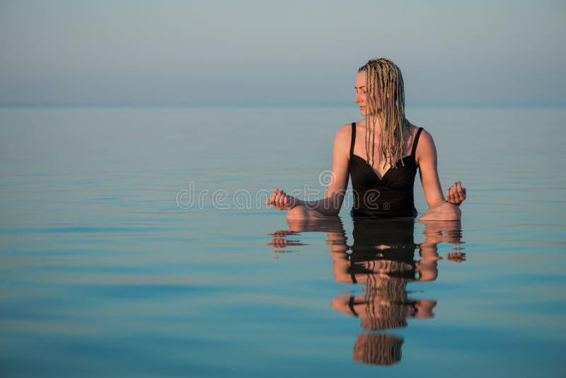 Женщина сидя в представлении йоги в штиль на море стоковые изображения