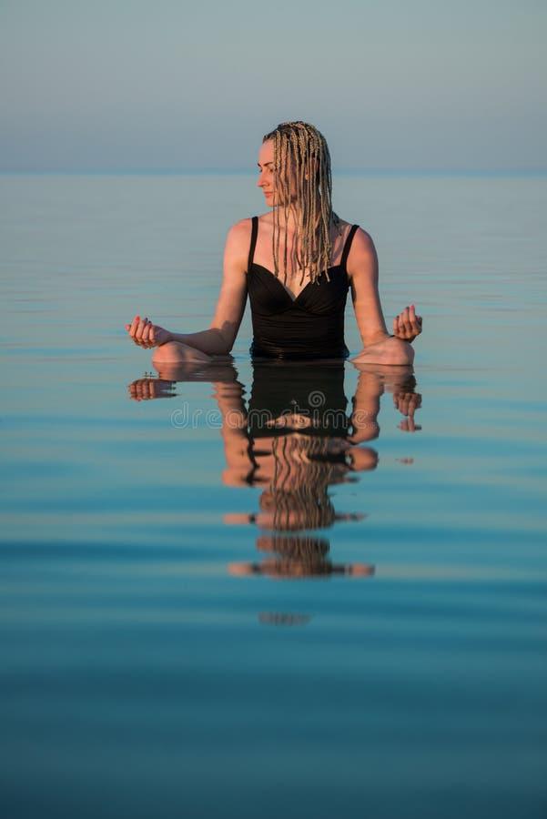Женщина сидя в представлении йоги в штиль на море стоковые фото