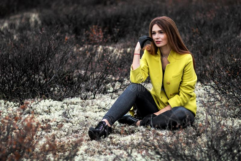 Женщина сидя в сухих черных кустах стоковая фотография