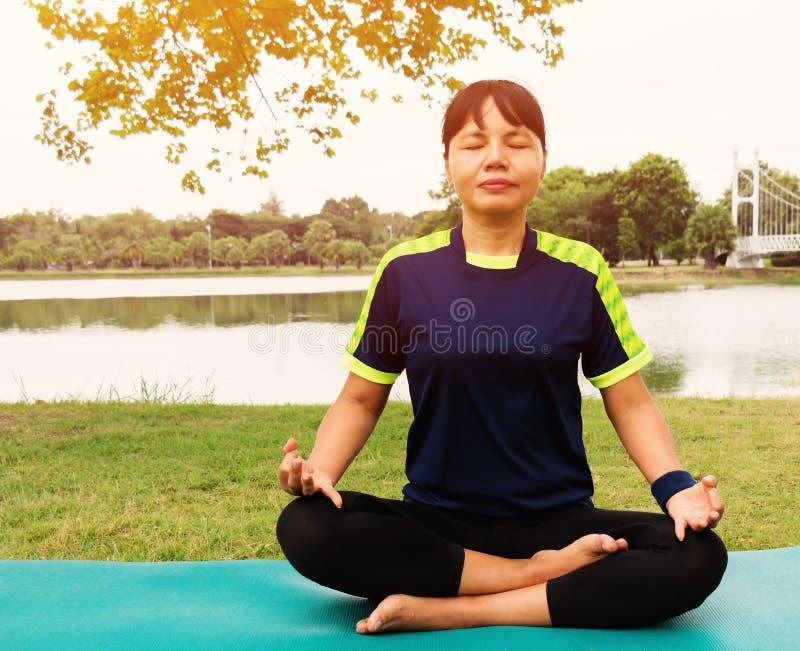 Женщина сидя для йоги в парке стоковые фотографии rf