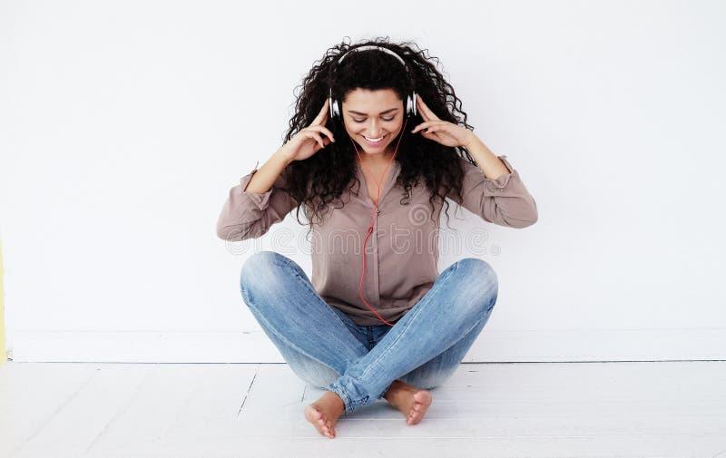 Женщина сидя дома и слушая к музыке с наушниками стоковая фотография