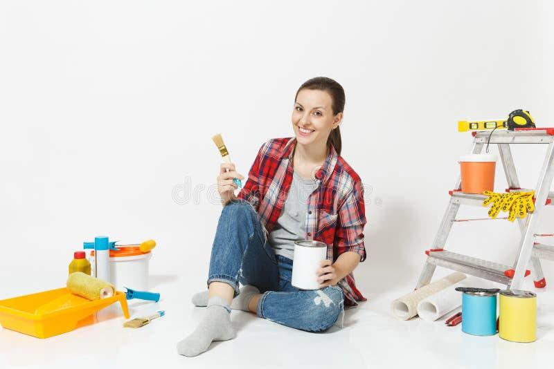 Женщина сидя на поле с щеткой, консервной банкой краски, аппаратурами для комнаты квартиры реновации изолированной на белой предп стоковое фото