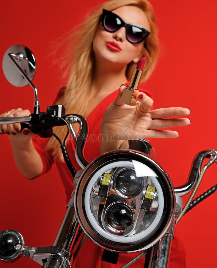 Женщина сидя на современном велосипеде мотоцикла в солнечных очках и показать красную губную помаду стоковое фото rf