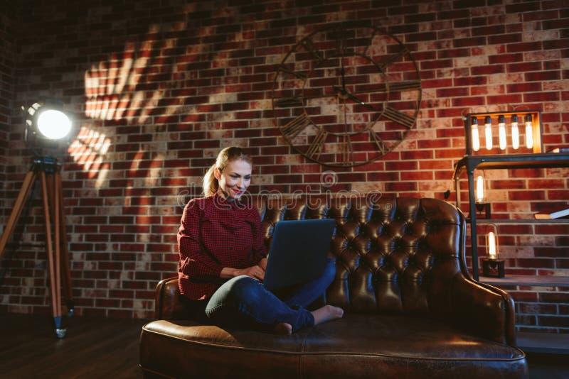 Женщина сидя на софе lather в интерьере просторной квартиры работа на lapt стоковое фото rf