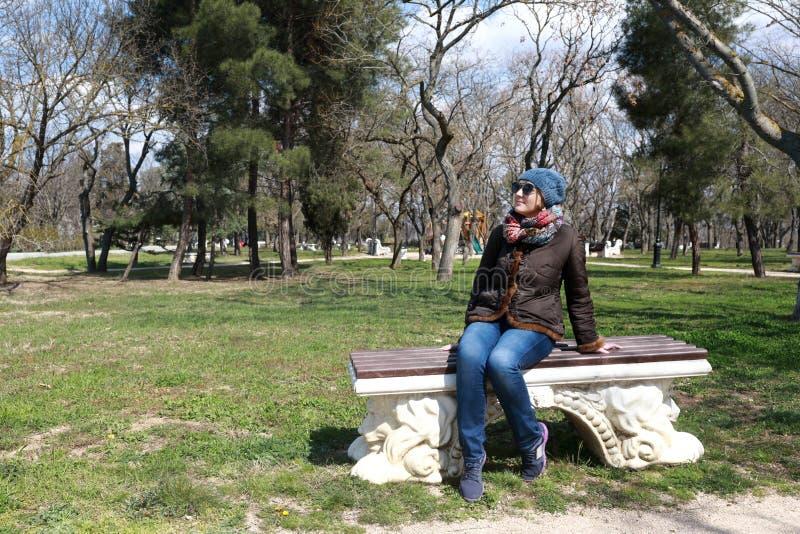 Женщина сидя на стенде весной стоковые фотографии rf