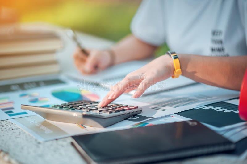 Женщина сидя на столе и работая под рукой книги и финансовая стоковое изображение