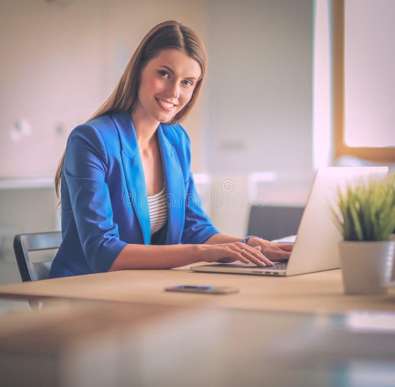 Женщина сидя на столе с компьтер-книжкой стоковое изображение rf