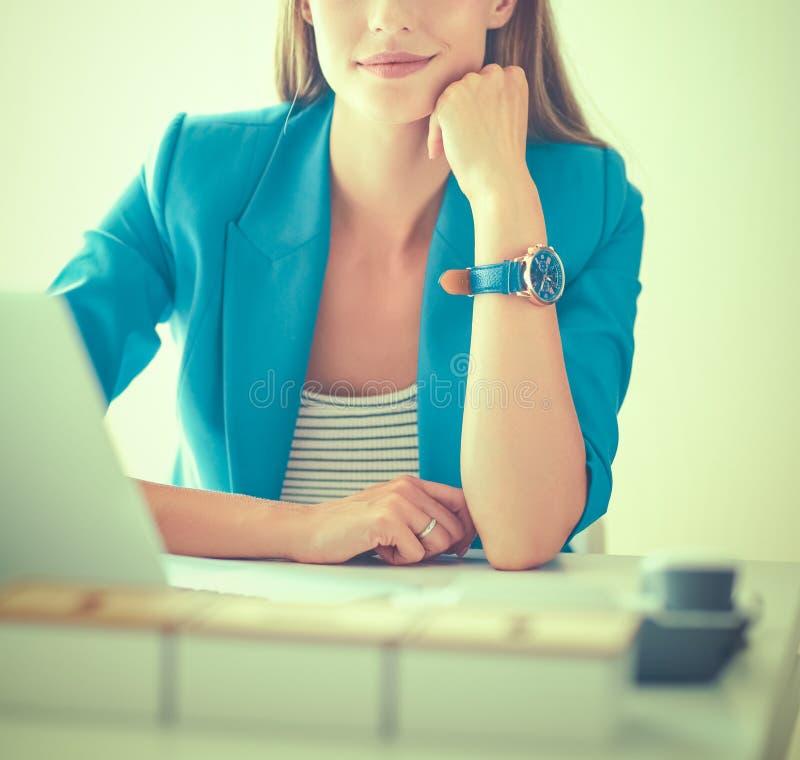 Женщина сидя на столе с ноутбуком стоковое изображение