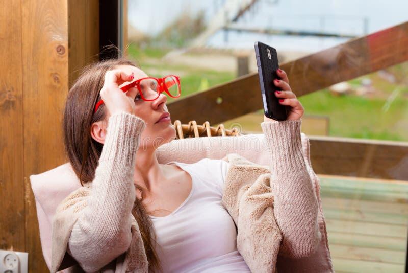 Женщина сидя на стуле используя телефон дома стоковое изображение rf