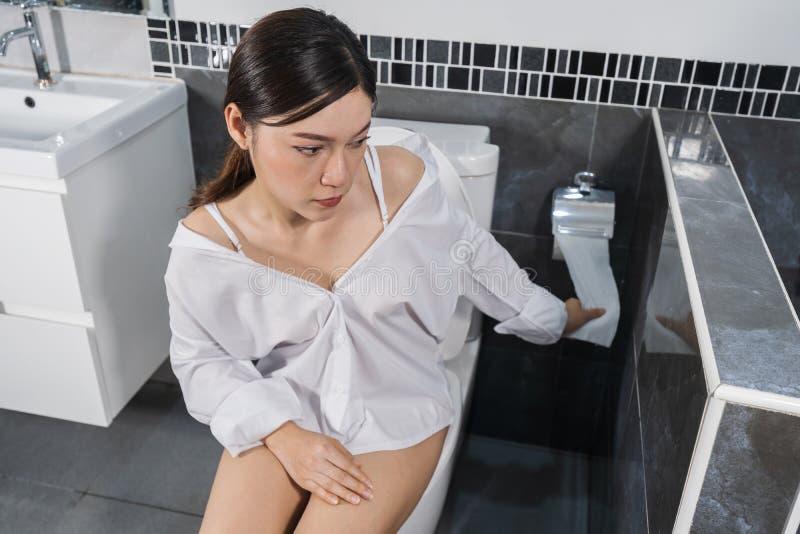 Женщина сидя на туалете и вытягивая бумажную ткань стоковое фото rf