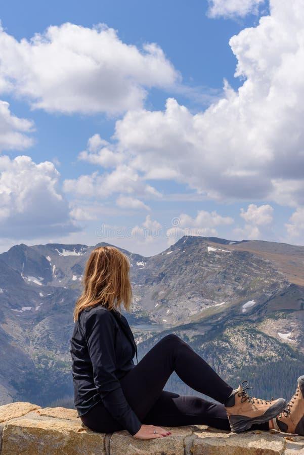 Женщина сидя на уступе смотря вне на скалистая горная цепь стоковые фотографии rf