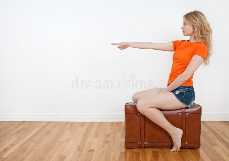 Женщина сидя на чемодане и указывая направлении стоковые фотографии rf