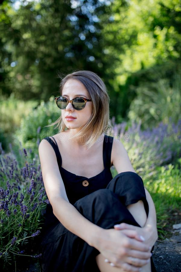Женщина сидя около цветков лаванды в саде стоковое фото