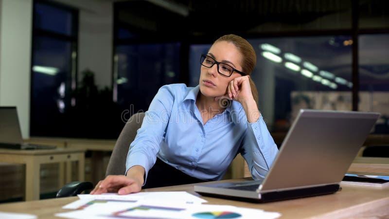 Женщина сидя расстроенная ненавидя работа пока работающ ночная смена в офисе, дополнительное время стоковые изображения rf