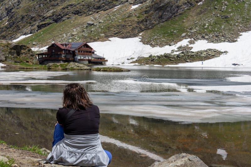 Женщина сидя созерцательно на lakeshore стоковые изображения