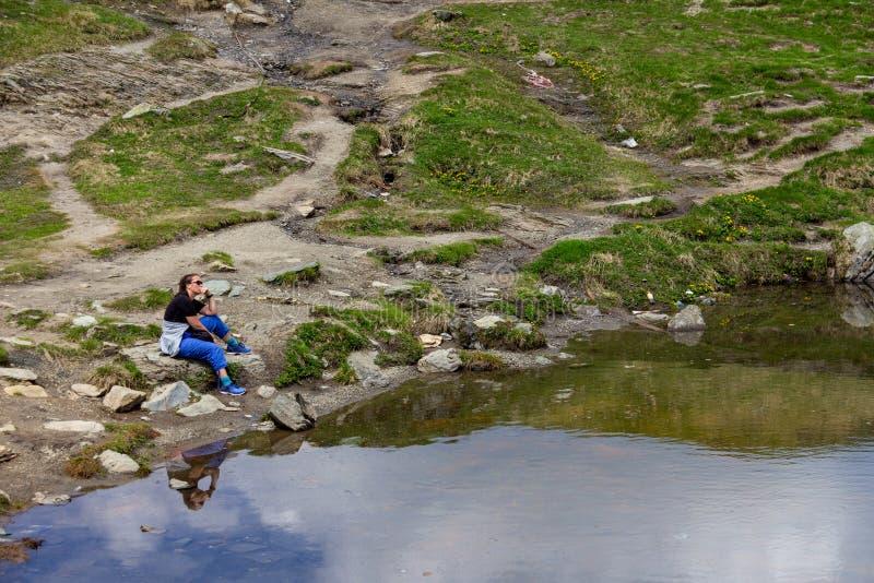 Женщина сидя созерцательно на lakeshore стоковые изображения rf