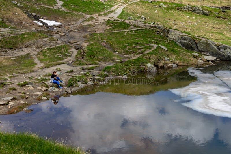 Женщина сидя созерцательно на lakeshore стоковая фотография rf