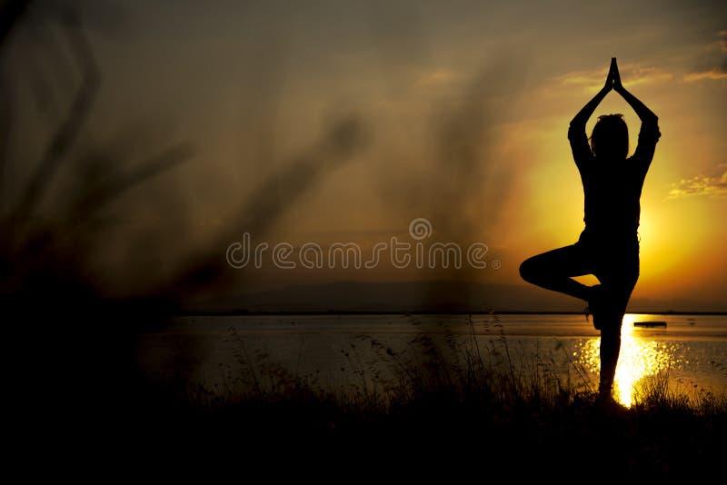 Женщина силуэта стоя на одной ноге стоковые изображения