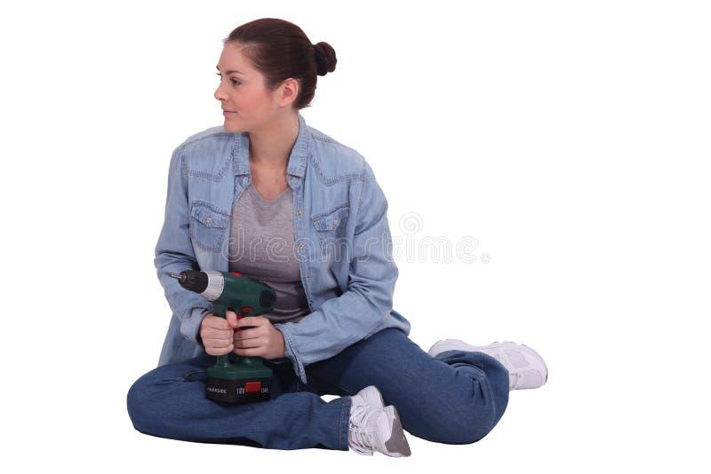 Женщина сидеть с электрической дрелью стоковое изображение rf