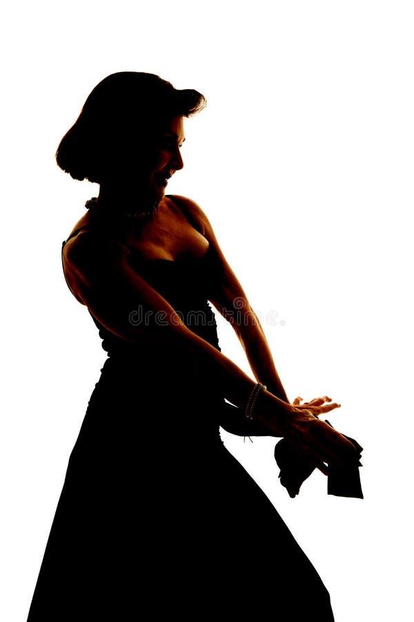 Женщина силуэта в платье вручает вне стоковое фото