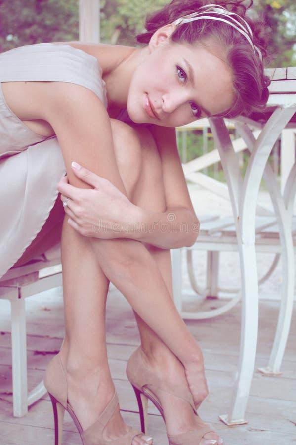 Женщина сидя в газебо нося бежевое silk платье стоковые изображения rf