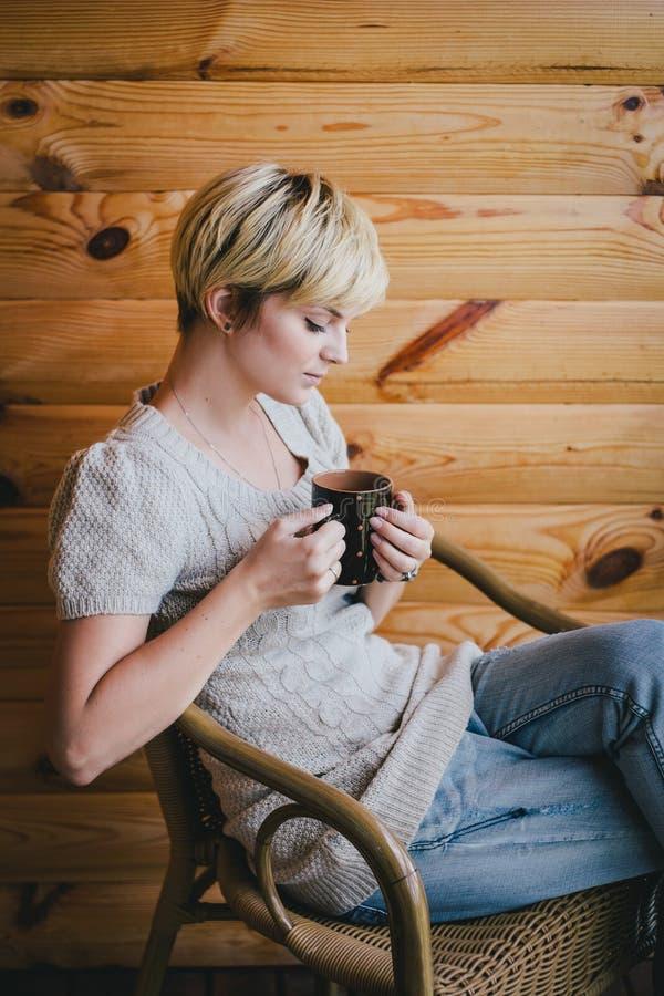 Женщина сидя в плетеном стуле на балконе с чашкой чаю стоковое фото