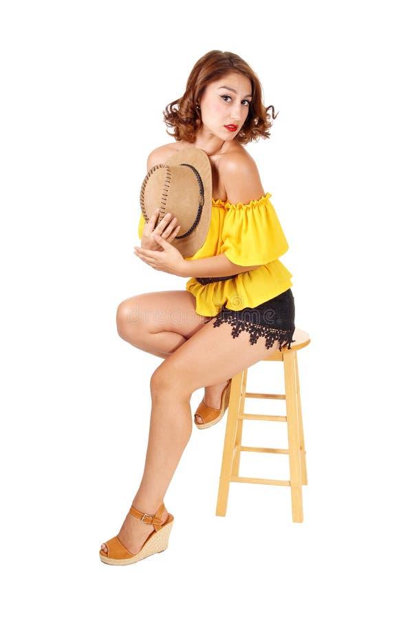 Женщина сидя в шортах и шляпе стоковое фото
