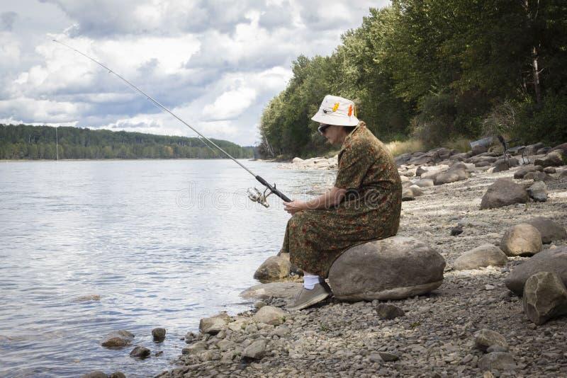 Женщина сидя на береге на рыбной ловле утеса стоковое фото