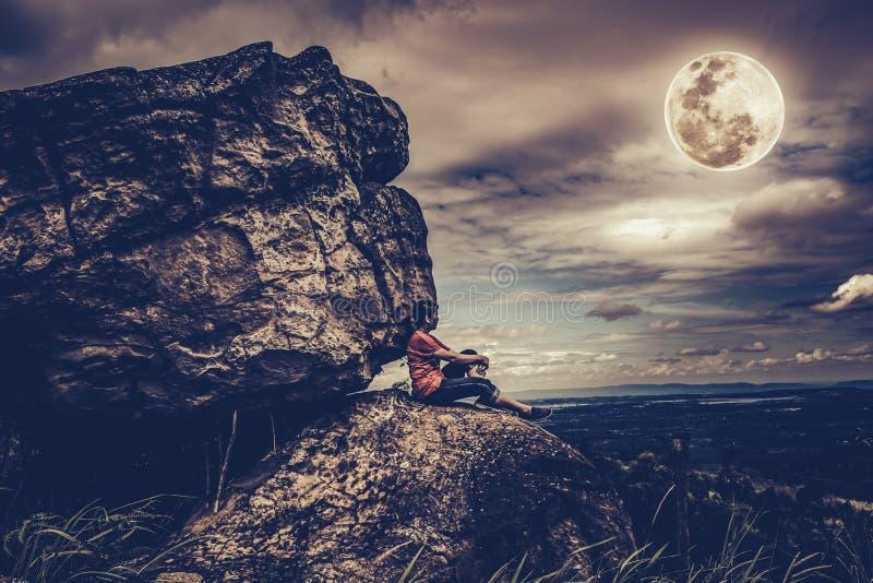 Женщина сидя на валунах, небе с пасмурным и полнолунии Низкий ke стоковая фотография