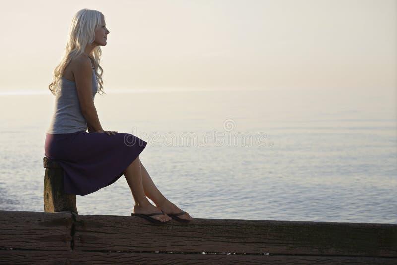 Женщина сидя на деревянной связке на пляже стоковое изображение rf