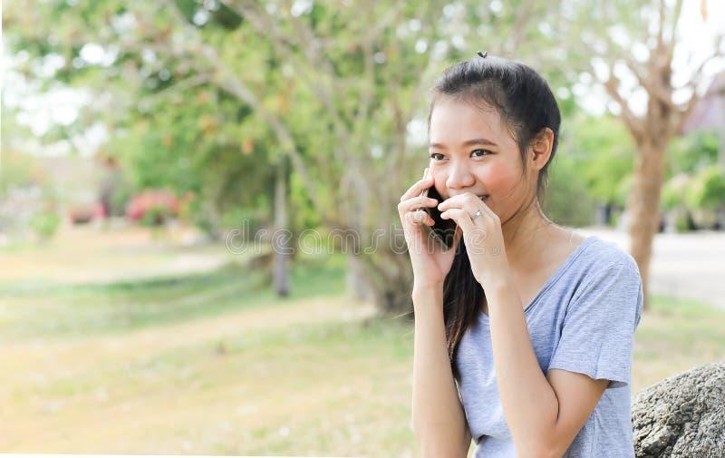 Женщина сидя на камне используя мобильный телефон стоковое фото