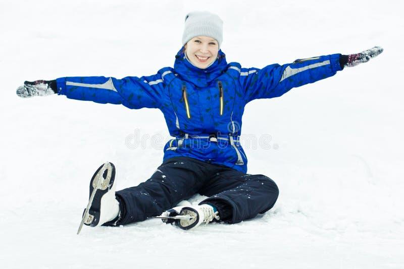 Женщина сидя на коньках льда. стоковая фотография