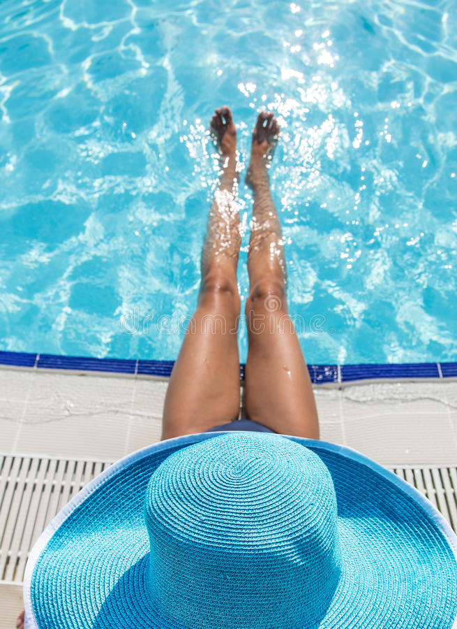 Женщина сидя на крае бассейна стоковое изображение rf