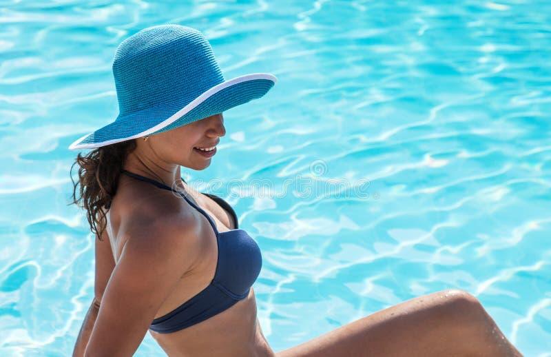 Женщина сидя на крае бассейна стоковые фото
