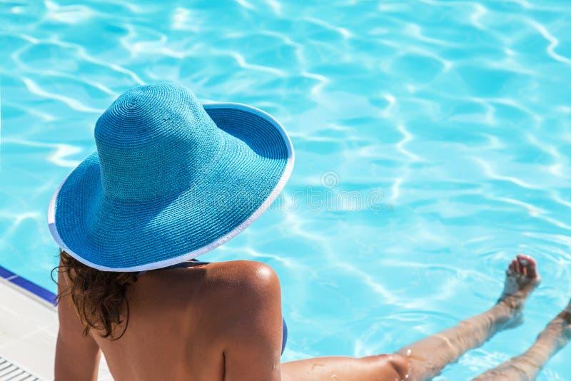 Женщина сидя на крае бассейна стоковая фотография rf