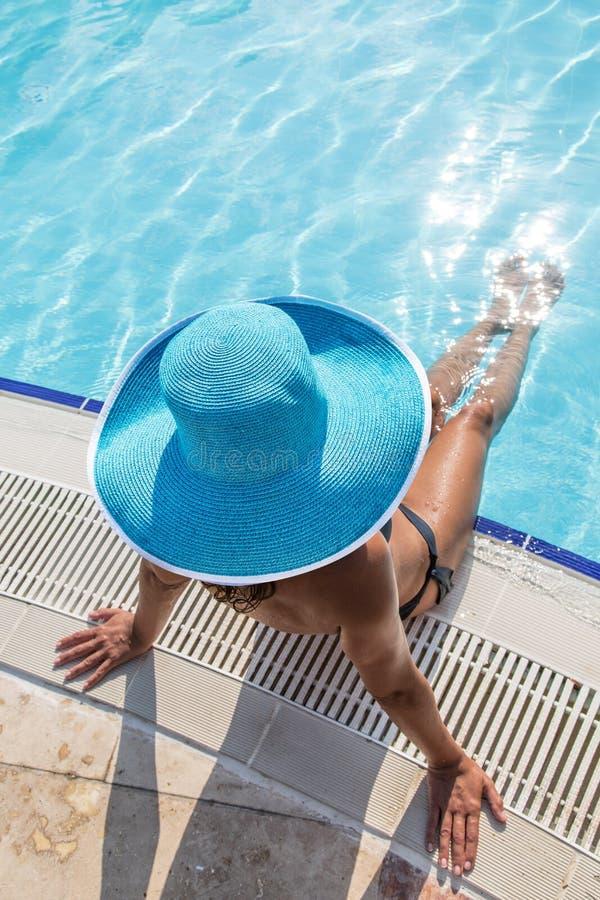 Женщина сидя на крае бассейна стоковое изображение