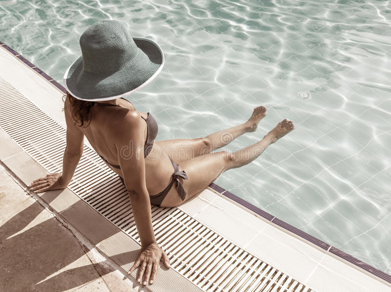 Женщина сидя на краю бассейна стоковое изображение