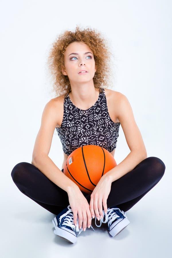 Женщина сидя на поле с шариком баскетбола стоковая фотография rf