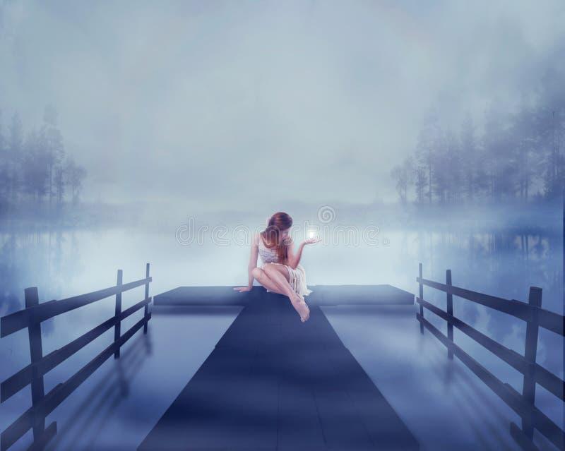 Женщина сидя на пристани озера с ярким шариком накалять светлым в ее руке стоковые фотографии rf