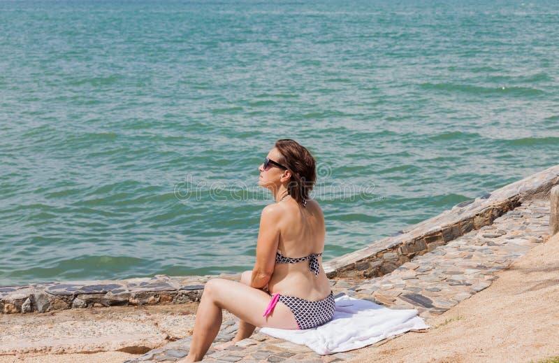 Женщина сидя на скалистой береговой линии стоковая фотография
