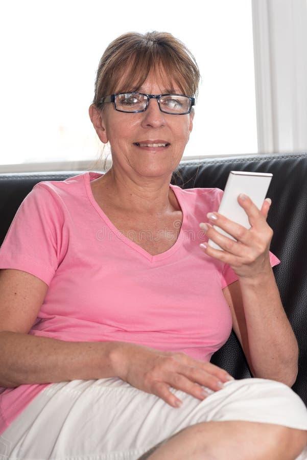 Женщина сидя на софе и используя ее мобильный телефон стоковые фото
