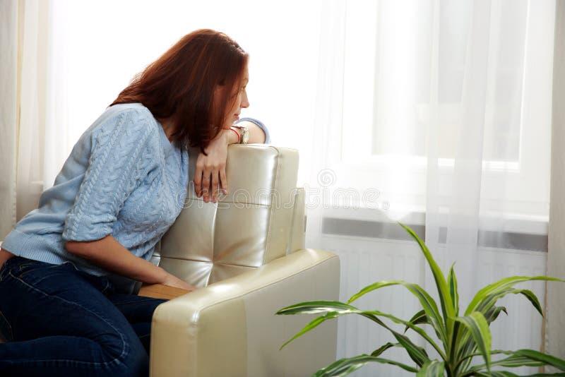 Download Женщина сидя на софе и смотря в окне Стоковое Изображение - изображение насчитывающей полагаться, нутряно: 37926861