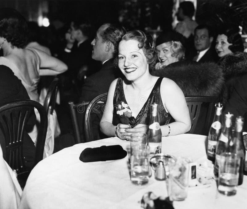Женщина сидя на таблице в клубе (все показанные люди более длинные живущие и никакое имущество не существует Гарантии поставщика  стоковое изображение