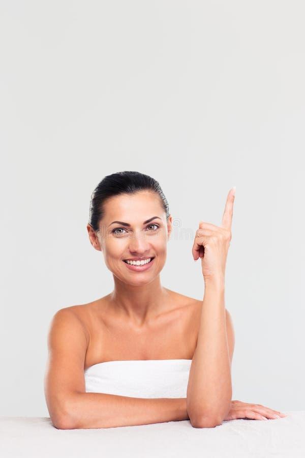 Женщина сидя на таблице и показывая палец вверх стоковая фотография