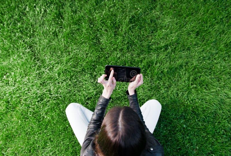 Женщина сидя на траве и используя таблетку стоковая фотография rf