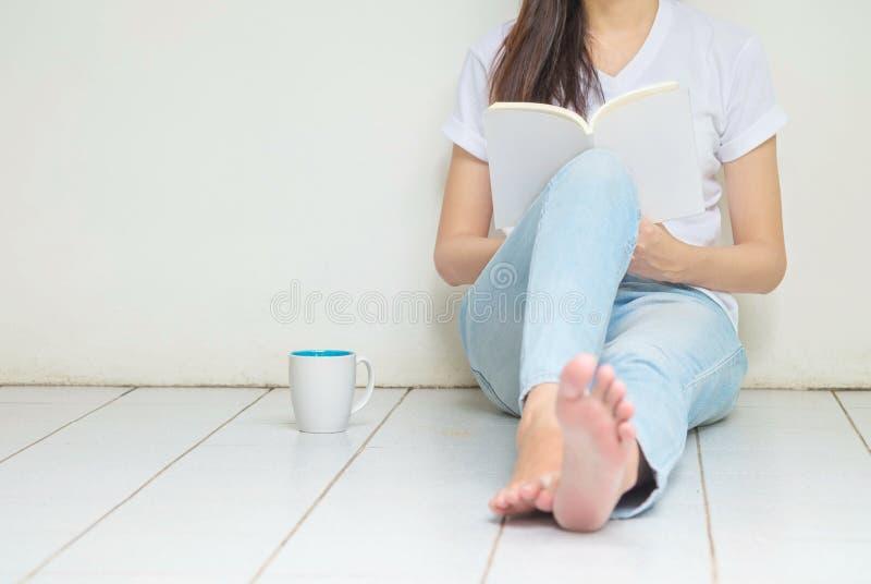 Женщина сидя на угле дома для читать книгу в свободном времени в после полудня, ослабляет время азиатской женщины стоковые фотографии rf