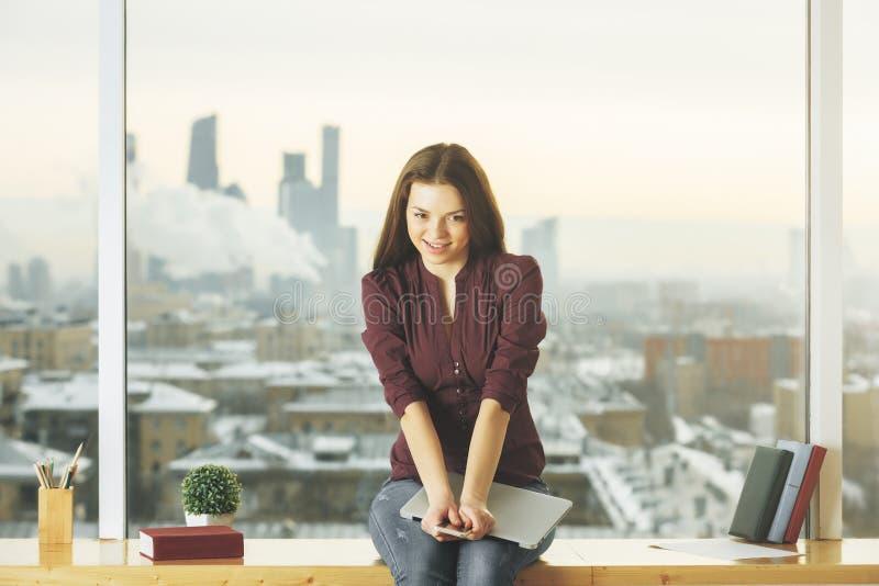 Женщина сидя на windowsill стоковые изображения