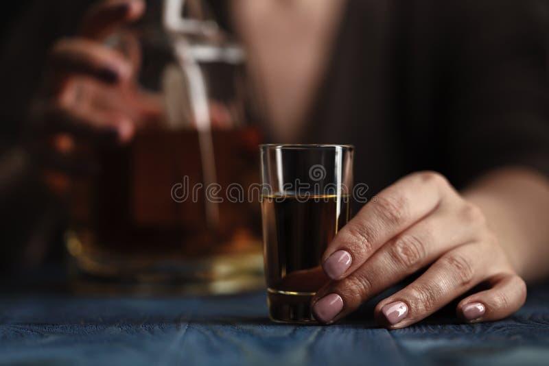 Женщина сидя дома выпивающ слишком много вискиа, она addi стоковая фотография