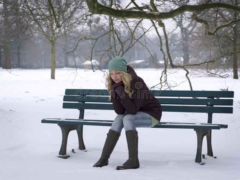 Женщина сидя самостоятельно на скамейке в парке в зиме стоковые фотографии rf